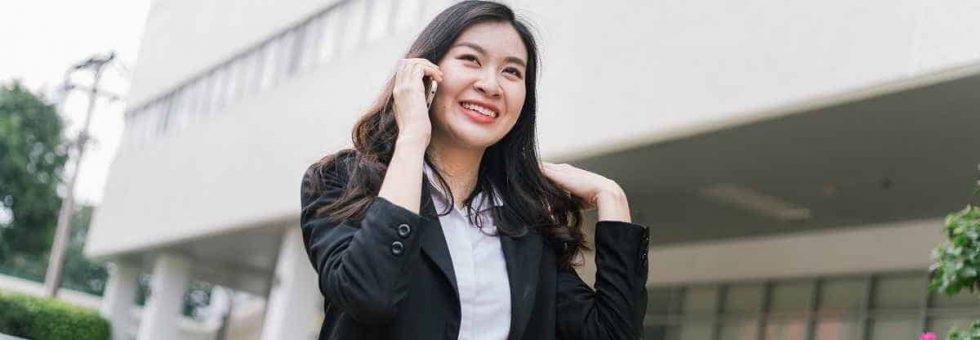 Beautiful asian business woman talking on cellphone while walkin