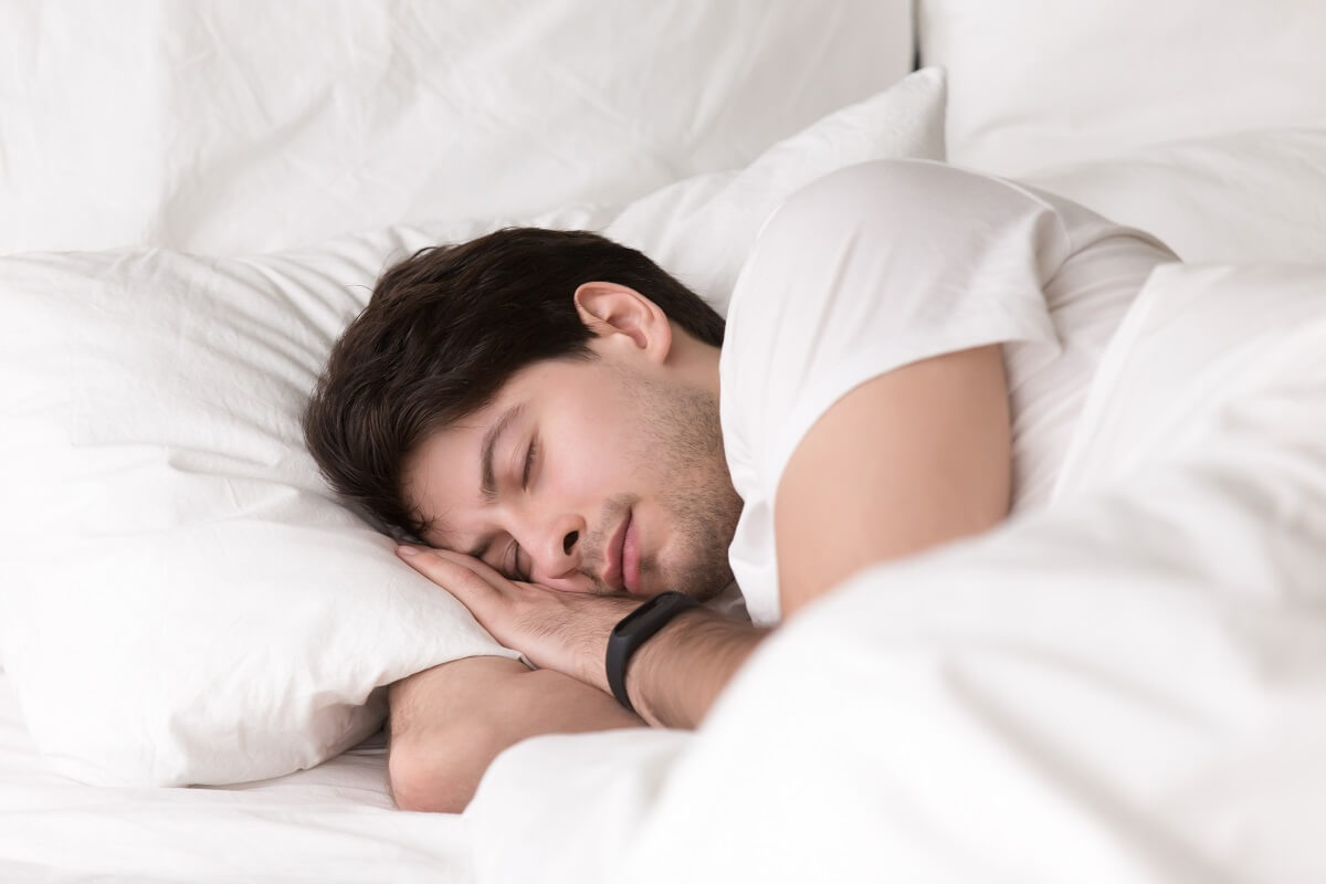 Young guy sleeping in bed wearing smartwatch or sleep tracker