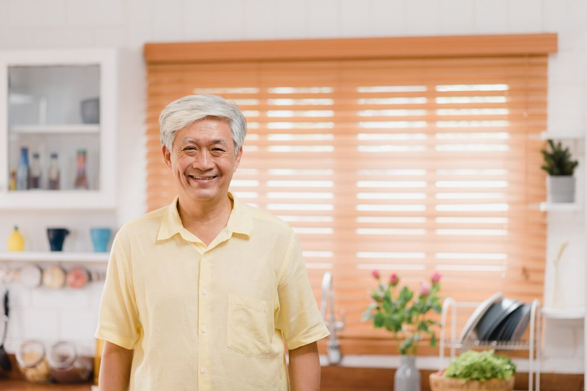 Asian elderly man feeling happy smiling and looking to camera wh