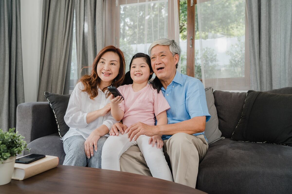 Asian grandparents watch TV with granddaughter at home. Senior C