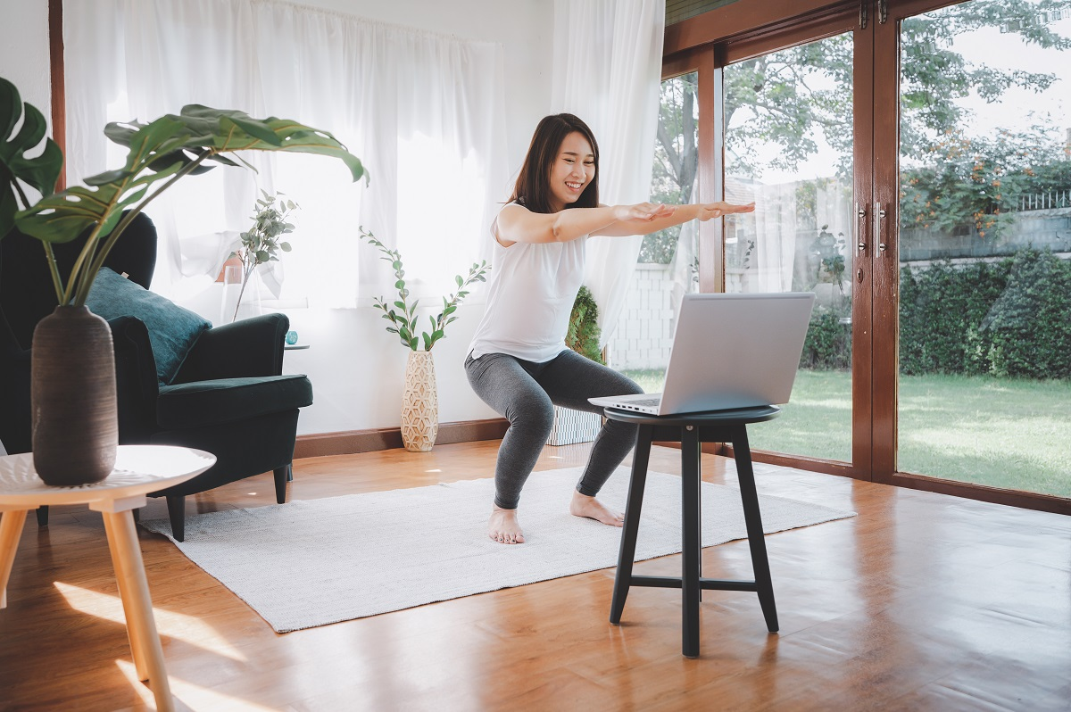 woman learned online workout excercise class at home from laptop