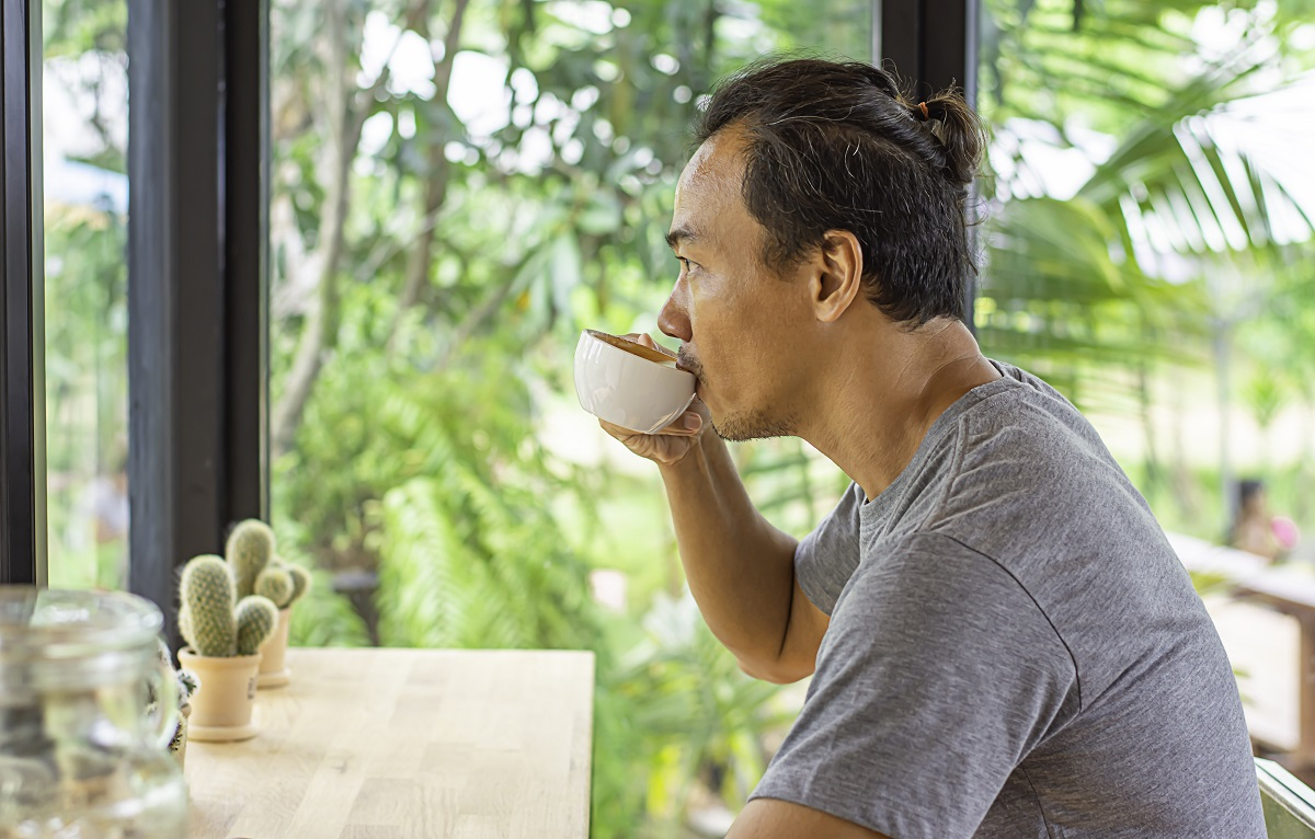 Asian man holding a coffee cup in hand And drinking Background