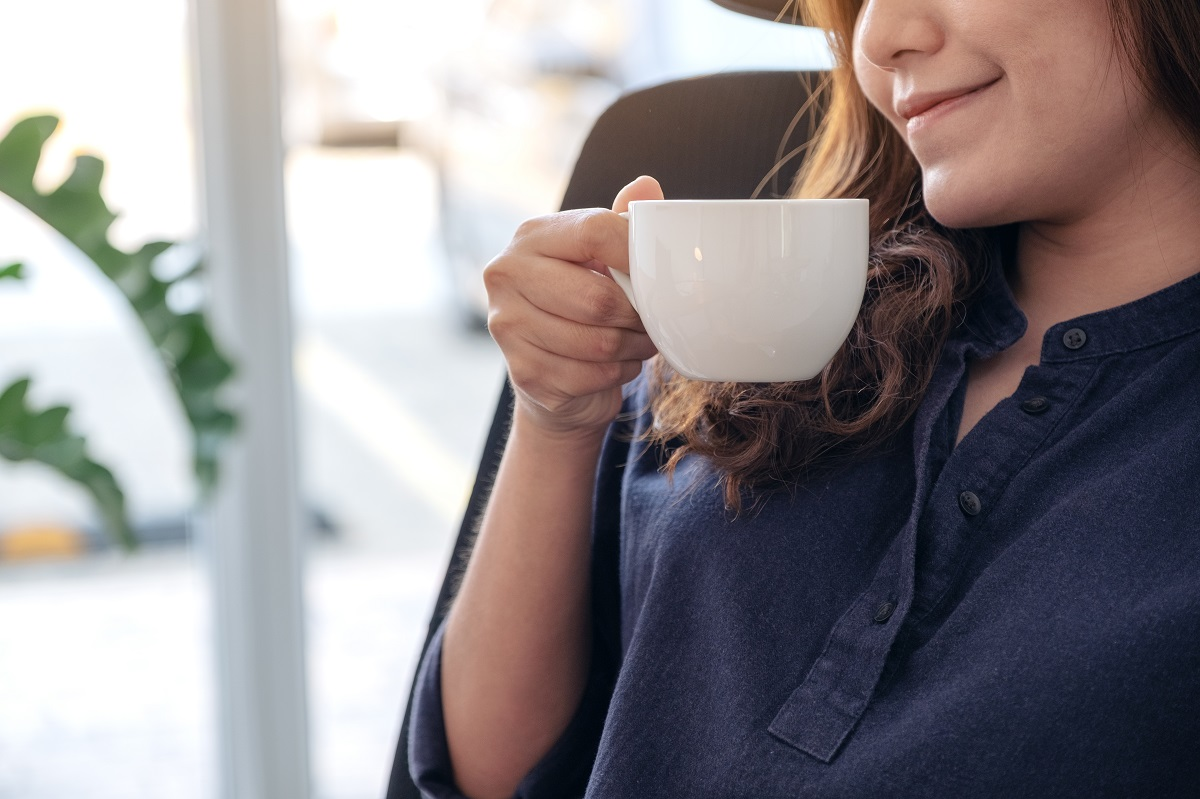 A beautiful Asian woman holding and drinking hot coffee with fee